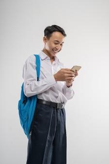 バックパック付きの携帯電話を見ている中学生の制服を着た少年
