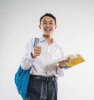 중학교 교복을 입은 소년이 엄지 손가락으로 책을 들고 미소 짓는다.