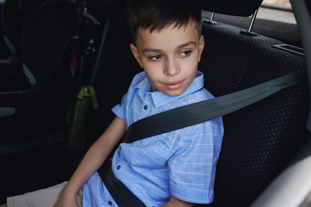 シートベルトを着用した少年は、保護用のチャイルドシートで移動します。子供と一緒に安全に旅行する。車内でのお子様の安全な移動