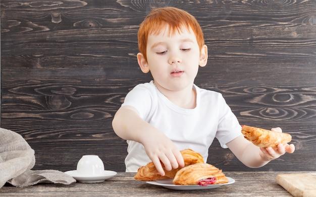 小麦パフの白いお団子と赤いチェリージャムで作ったデザートを黒で食べている少年