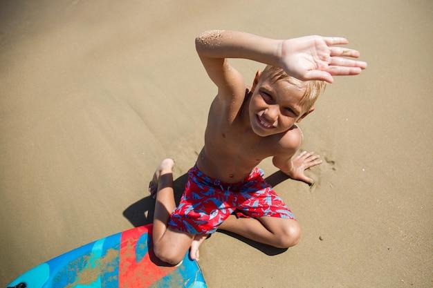 Мальчик с бодибордом на волне
