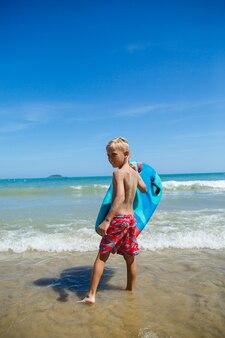 波にボディーボードを持つ少年