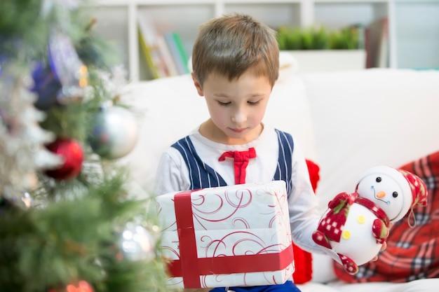 クリスマスプレゼントを持った男の子。クリスマスプレゼントをもらおう。子供は贈り物を受け取りました
