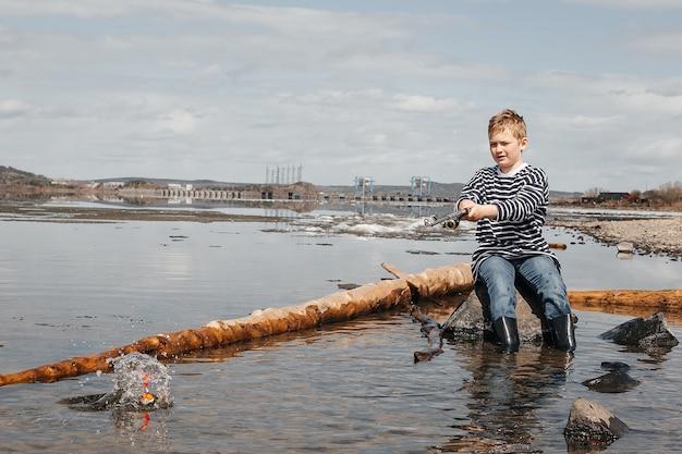 釣り竿を持った少年が川のほとりに座って釣りをしている。縞模様のベストを着たハンサムな男の子が釣り竿を手に座っています