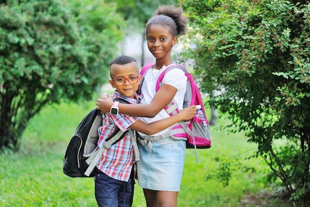 학교 가방을 든 아프리카 계 미국인 자매가있는 소녀 또는 형제가있는 소년 포옹 ...