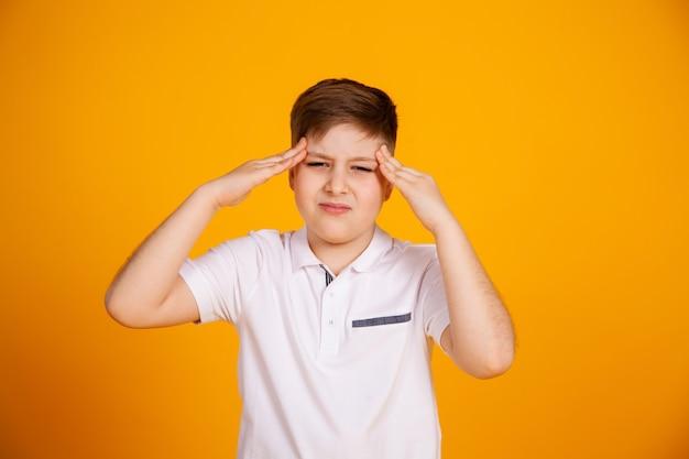 頭痛の少年。頭痛や片頭痛に苦しんでいる黄色の背景に白人の子供。