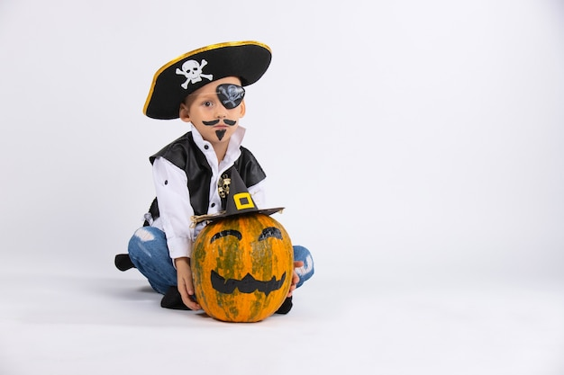 海賊の帽子をかぶった真面目な顔の少年。近くには黒い手作りの帽子をかぶったカボチャがあります。どちらもバラ色のメイクです。