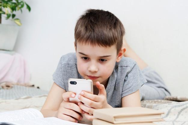 ベッドで本の横にスマートフォンを持っている男の子がレッスンを教えています。インターネットを介したオンライン遠隔学習