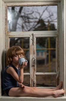 Мальчик со светлыми волосами сидит на старом обшарпанном подоконнике и пьет из железной кружки.