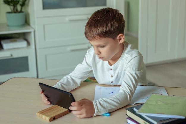 Мальчик с темными волосами в белой рубашке сидит за столом и делает домашнее задание с помощью планшета.