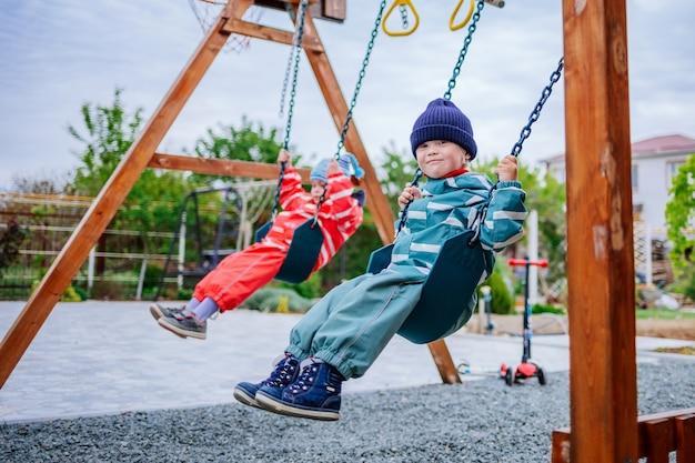 다운 증후군을 앓고있는 한 소년이 놀이터에서 놀다가 스윙을하고있다. 어린이의 유전병. 선택적 초점