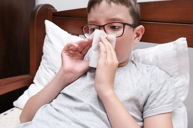 Мальчик с гриппом и лихорадкой, лежащий в постели и сморкающийся бумажной салфеткой, концепция сезонных вирусных заболеваний.