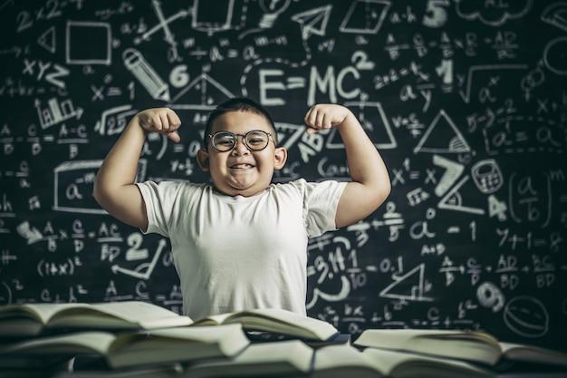Мальчик в очках сидит в кабинете и держит обе руки перпендикулярно