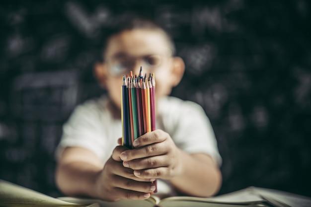 多くの色鉛筆で座っている眼鏡の少年