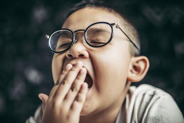 Мальчик в очках учится и дремлет.