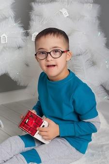 ダウン症の眼鏡をかけた少年がテーブルに座っておもちゃで遊ぶ