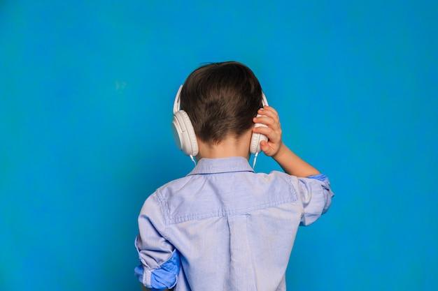 青い背景にヘッドホンを持っている男の子子供用ヘッドホン子供のためのヘッドホンの害