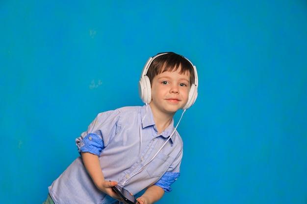 青い背景にヘッドホンを持っている男の子子供用ヘッドホンヘッドホンの害