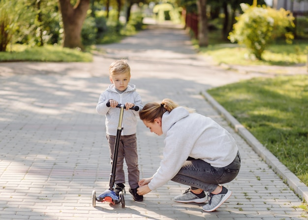 Мальчик с мамой катается в скутере по парку