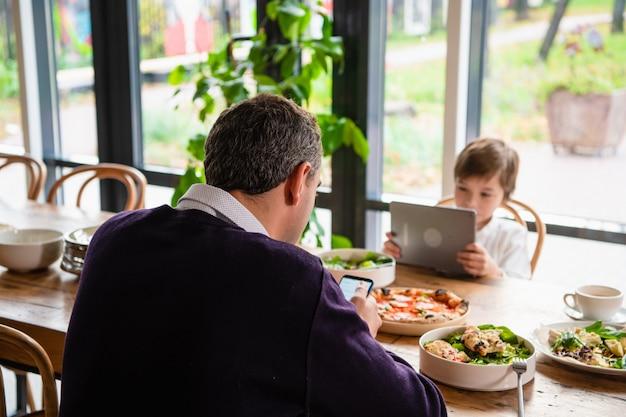 夕食の席に座っているタブレットを持つ少年