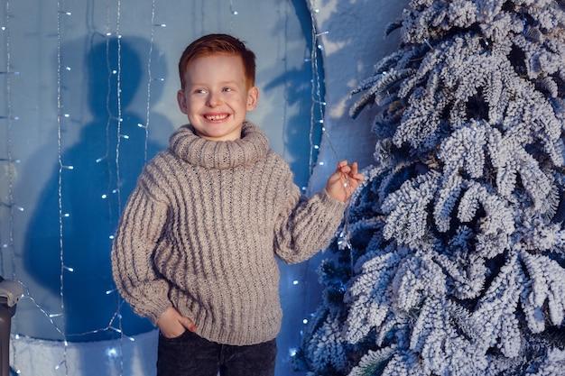 Мальчик с рыжими волосами и веснушками на синем фоне и заснеженном дереве