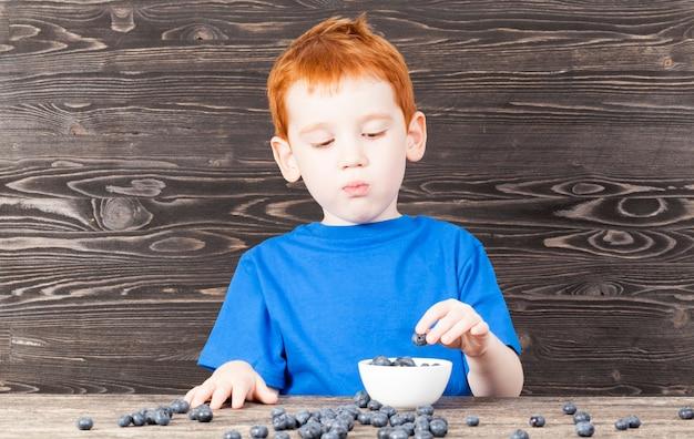 빨간 머리와 주근깨를 가진 소년은 접시, 부엌, 검은 색 식탁에 블루 베리 열매를 넣습니다.