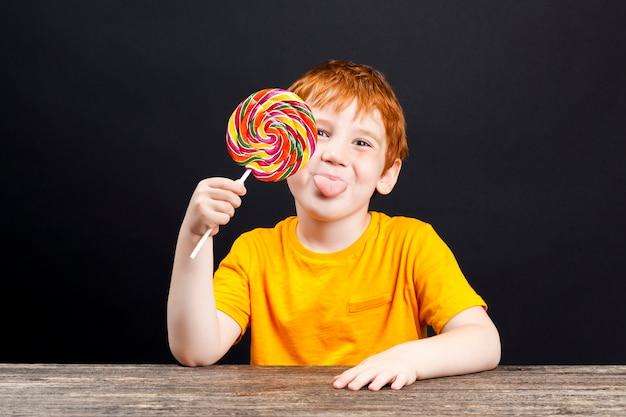빨간 머리를 가진 소년이 달콤한 멀티 컬러 캔디 롤리팝을 먹는다.