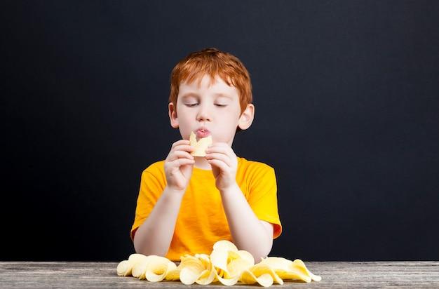 빨간 머리를 가진 소년이 먹으면서 바삭하고 맛있는 감자 칩을 먹고 수집