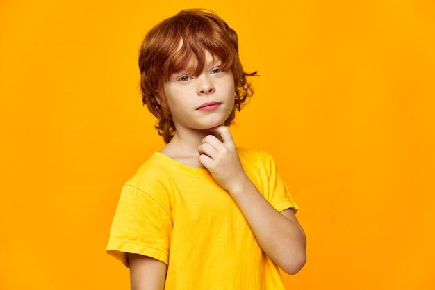 赤い髪の少年が顔の近くで手を握っている