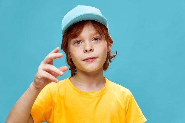 Мальчик с рыжими волосами жестикулирует руками в желтой футболке