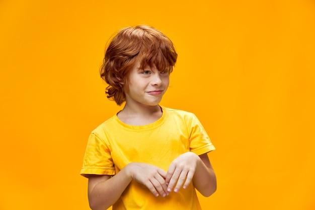 Мальчик с рыжими волосами улыбается и смотрит в сторону