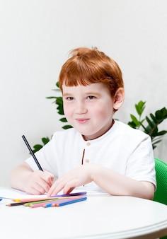 공부하거나 일하는 동안 빨간 머리를 가진 소년, 소년은 종이에 색연필로 그립니다.