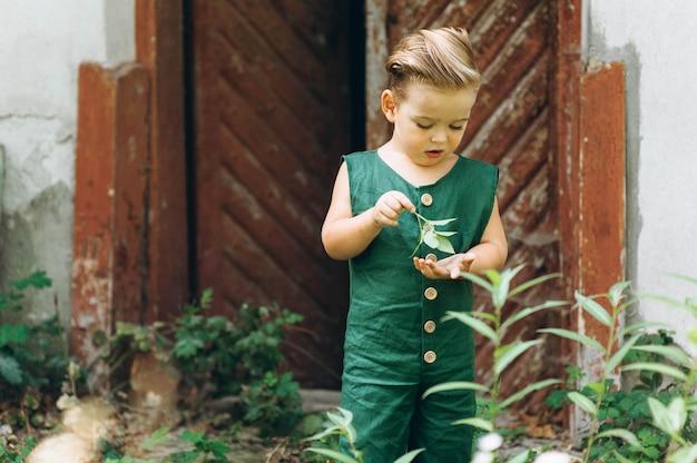 緑の組み合わせで白い髪の少年が木製の古いドアの横で遊ぶ