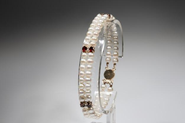 天然真珠、ガーネット、ダイヤモンドにゴールドの留め金が付いたブレスレット。イエローゴールドと貴石