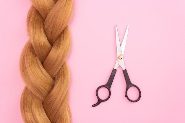 Коса из русых искусственных волос на розовой поверхности и ножницы