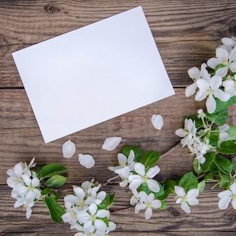 Ветка цветущей яблони с белыми цветами и листом бумаги на деревенском деревянном фоне, с копией пространства, вид сверху