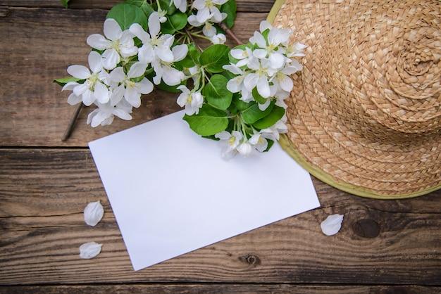 Ветка цветущей яблони с белыми цветами, листом бумаги и соломенной шляпой на деревенском деревянном фоне, с копией пространства, вид сверху