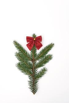 Ветка елки украшена красным бантом на белом.
