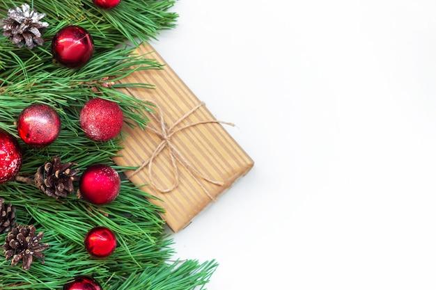 공예 포장지에 있는 선물 상자 근처에 장난감 공과 원뿔이 있는 크리스마스 트리 가지