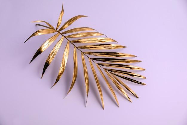 白いテーブルの上に金で作られたヤシの木の枝。
