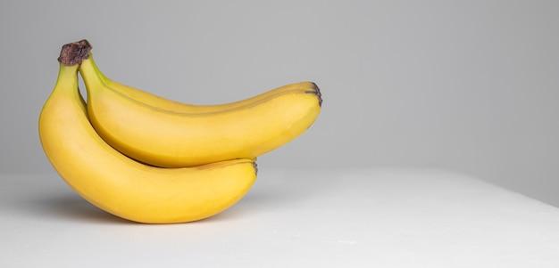 Ветка бананов на серой поверхности. фрукты. экзотический фрукт. фрукты в студии. копировать пространство