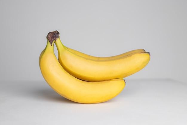 Ветка бананов на серой стене. фрукты. экзотический фрукт. фрукты в студии. копировать пространство