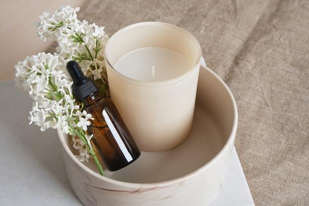 천연 린넨 배경 복사 공간에 있는 세라믹 그릇에 흰색 라일락 가지, 유리에 아로마 양초, 아로마 오일이 든 갈색 병