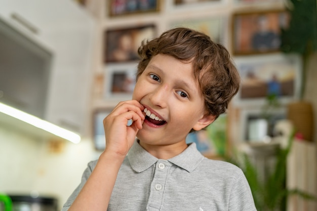 Храбрый маленький мальчик 7 лет качает своим молочным зубом.