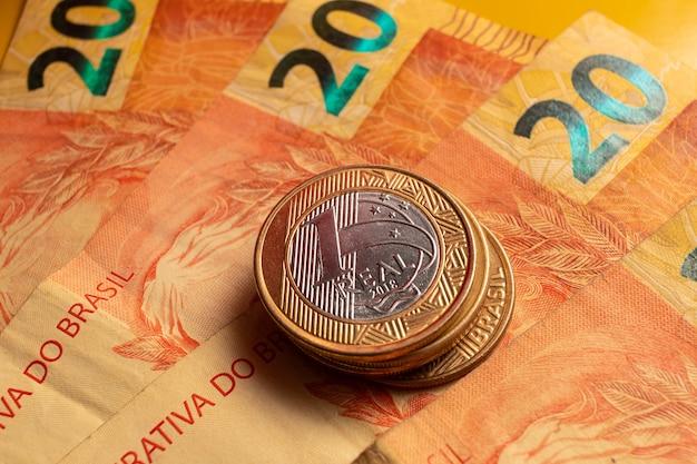 ブラジルの本物の紙幣とブラジルの硬貨emは上面図で写真をクローズアップ