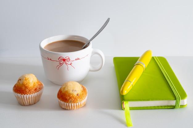 Завтрак, состоящий из кофе и двух маффинов с перьевой ручкой и блокнотом.