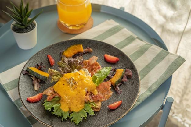Завтрак или бранч, яйца бенедикт подаются с жареным беконом и тостами, украшаются ломтиками клубники и тыквы в черном блюде или тарелке на белой ткани с зеленой полосой и идут с апельсиновым соком.