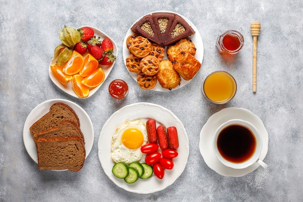 Блюдо для завтрака, содержащее коктейльные сосиски, яичницу, помидоры черри, сладости, фрукты и стакан персикового сока.