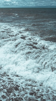 Громящая волна и бурное море в формате вертикальной панорамы.