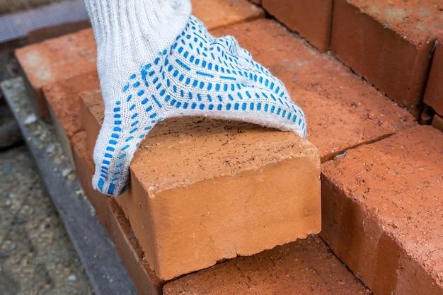 Каменщик берет кирпичи с поддона, чтобы построить свой дом